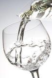 Água que derrama no vidro Imagem de Stock
