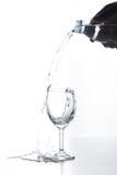 Água que derrama no vidro isolado Foto de Stock Royalty Free