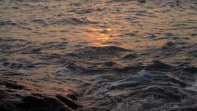Água que espirra contra rochas com o por do sol filme