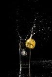 A água que espirra fora de um vidro como um cubo de gelo é deixada cair dentro à Foto de Stock Royalty Free