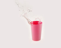 Água que espirra no copo plástico Imagens de Stock Royalty Free