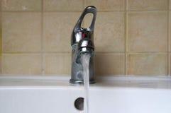 Água que flui de uma torneira velha Fotos de Stock