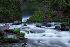 Água que flui em torno das rochas Imagens de Stock Royalty Free