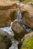 Água que flui entre rochas Fotografia de Stock