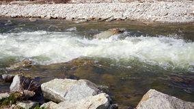 A água que flui no rio selvagem pequeno durante a primavera, sol brilha nas ondas brancas, nas pedras no primeiro plano e no fund filme