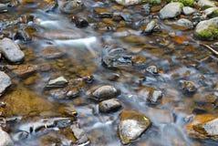 Água que flui sobre pedras Fotos de Stock