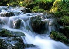 Água que flui sobre rochas.