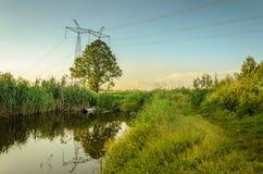 Água que jorra do esgoto ao rio/conceito da ecologia: o esgoto derrama desperdiça para fora ao rio imagem de stock royalty free