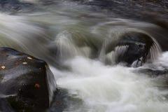 Água rapidamente de fluxo através das grandes rochas em uma paisagem da queda foto de stock