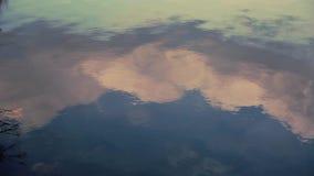 Água Rippling no lago com uma reflexão das nuvens vídeos de arquivo