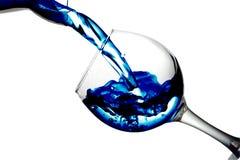 A água roxa derrama em um vidro em um fundo branco foto de stock royalty free