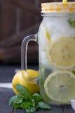 Água saudável com hortelã, os limões cortados e os pepinos Bebida da dieta Água Sassy Frasco de pedreiro completamente com frutas Fotos de Stock