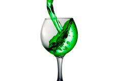 A água verde derrama em um vidro em um fundo branco Fotografia de Stock