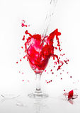 A água vermelha derrama vidro de vinho quebrado em um fundo branco Imagem de Stock