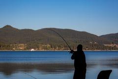 Águas azuis e montanha da silhueta do pescador imagens de stock royalty free