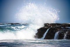 Águas azuis puras do Oceano Pacífico de Califórnia, ondas litorais que quebram e que espirram nas rochas da costa de mar Encrusted Foto de Stock