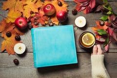 Álbum azul con el espacio para el texto y la taza del té, decoración de las hojas de otoño, manzanas en el tablero de madera Toda Fotografía de archivo libre de regalías