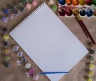 Álbum de dibujo con las pinturas del color en la tabla foto de archivo