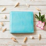 Álbum de foto azul de la familia para la foto del viaje del eco-cuero y concha marina alrededor en el tablero de madera Visión su foto de archivo libre de regalías