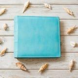 Álbum de foto azul de la familia para la foto del viaje del eco-cuero y concha marina alrededor en el tablero de madera Visión su imagenes de archivo