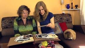 Álbum de foto viejo blanco del negro del reloj de la abuelita con su nieta almacen de metraje de vídeo