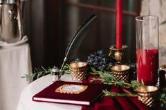 Álbum de la boda con la pluma de la tinta y velas en la tabla blanca Imagen de archivo libre de regalías