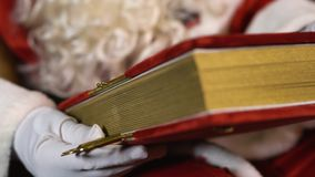 Álbum de seda vermelho velho da posse de Santa Claus perto da árvore de Natal com brinquedos e luzes filme