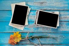 Álbum en blanco del marco de la foto con la flor en fondo de madera azul imagenes de archivo
