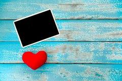 Álbum vazio do quadro da foto e coração vermelho no fundo de madeira azul Fotografia de Stock Royalty Free