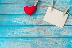 Álbum vazio do quadro da foto e suspensão vermelha do coração Fotografia de Stock