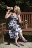 Álcool bebendo da mulher de uma garrafa de vidro no saco de papel Foto de Stock Royalty Free