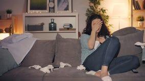 Álcool bebendo de grito da jovem mulher infeliz usando o smartphone que olha a tevê em casa filme
