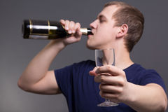 Álcool bebendo do homem novo sobre o fundo cinzento Imagem de Stock