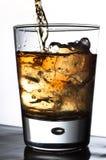 Álcool de derramamento em um vidro Fotografia de Stock Royalty Free