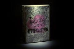 Ámele más letras negras del subtítulo en un fondo rosado del corazón Foto de archivo libre de regalías