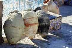 Ánforas tunecinas en el piso adornado con las baldosas cerámicas y la verja azul en Túnez Fotografía de archivo libre de regalías