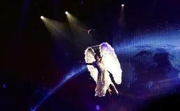 Ángel blanco en el fondo azul del planeta, proyectores de la etapa, funcionamiento aéreo Imagenes de archivo