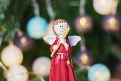 Ángel con la flauta delante de una rama de la Navidad adornada con c Fotos de archivo libres de regalías