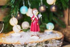 Ángel con la flauta delante de una rama de la Navidad adornada con c Fotografía de archivo libre de regalías