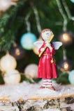 Ángel con la flauta delante de una rama de la Navidad adornada con c Fotos de archivo