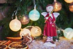 Ángel con la flauta delante de una rama de la Navidad adornada con i Fotografía de archivo libre de regalías