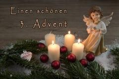 Ángel con las velas ardientes en la nieve y las bolas rojas de la Navidad Foto de archivo