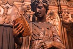 Ángel de la lectura que sostiene un libro viejo, estatua de madera en el santo del siglo XVII Charles Borromeo de la iglesia cató foto de archivo