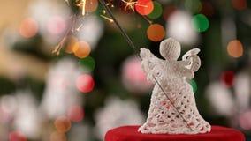 Ángel de la Navidad que sostiene la bengala delante de luces coloridas metrajes