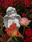 Ángel de rogación detrás de rosas Fotos de archivo libres de regalías