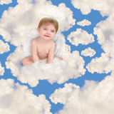 Ángel del bebé con las alas que se sientan en nubes Foto de archivo