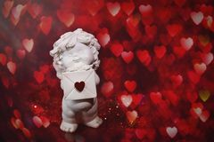 Ángel del bebé de la querube con el corazón y el bokeh imágenes de archivo libres de regalías