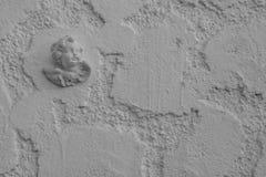 Ángel en el fondo de la pared blanca de la piedra Foto de archivo