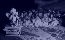 Ángel miniatura en un fondo azul oscuro Fotos de archivo