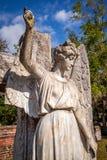 Ángel y cruz de piedra en un gravesite imagen de archivo
